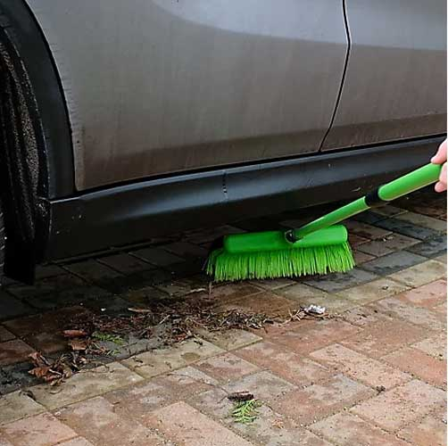 Telescopic rake broom sweeping debris from under car